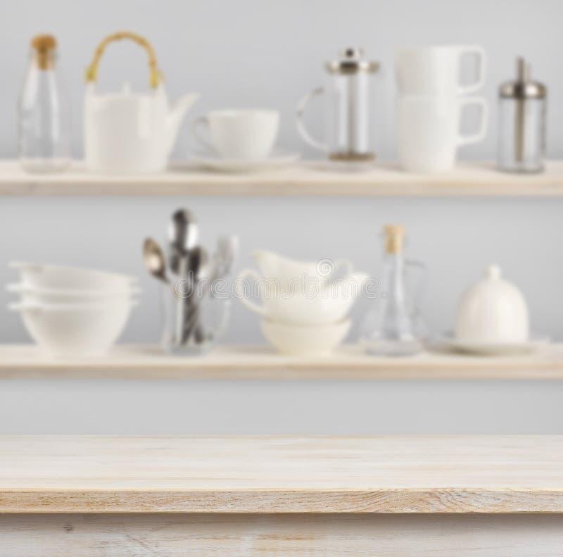 Drewniany stół nad tłem półki z kuchennymi naczyniami fotografia stock