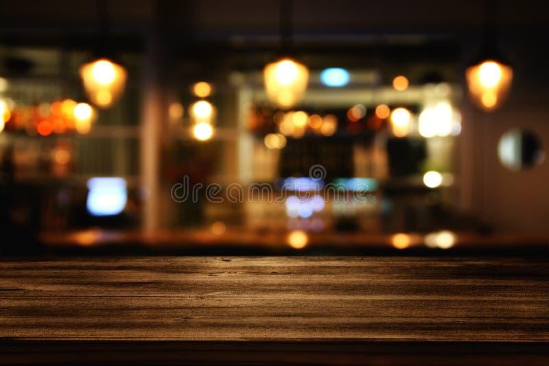 drewniany stół przed abstrakty zamazującymi restauracj światłami obraz stock