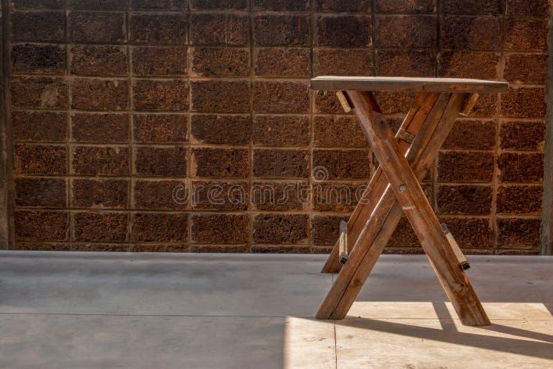 Drewniany stół z nogami jest listem X, światło słoneczne i tło jest laterytów ścianami zdjęcia royalty free