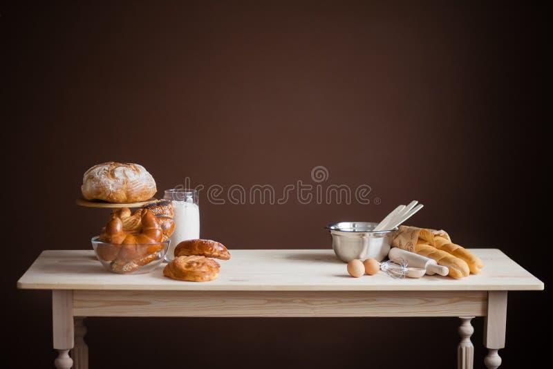 Drewniany st?? na br?zu tle z piec towarami, chleb, babeczki fotografia royalty free