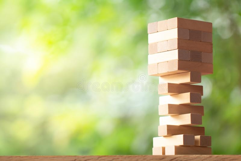 Drewniany sterty wierza od drewnianych bloków bawi się na greenery zamazującym tle zdjęcia stock