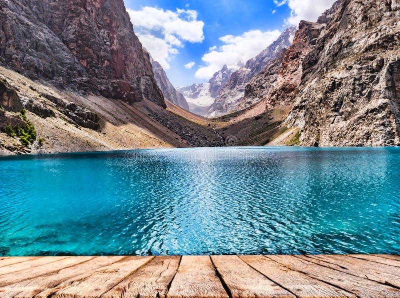 Drewniany stołowego wierzchołka i góry jezioro z turkus wodą w świetle słonecznym na skalistej góry tle obrazy stock