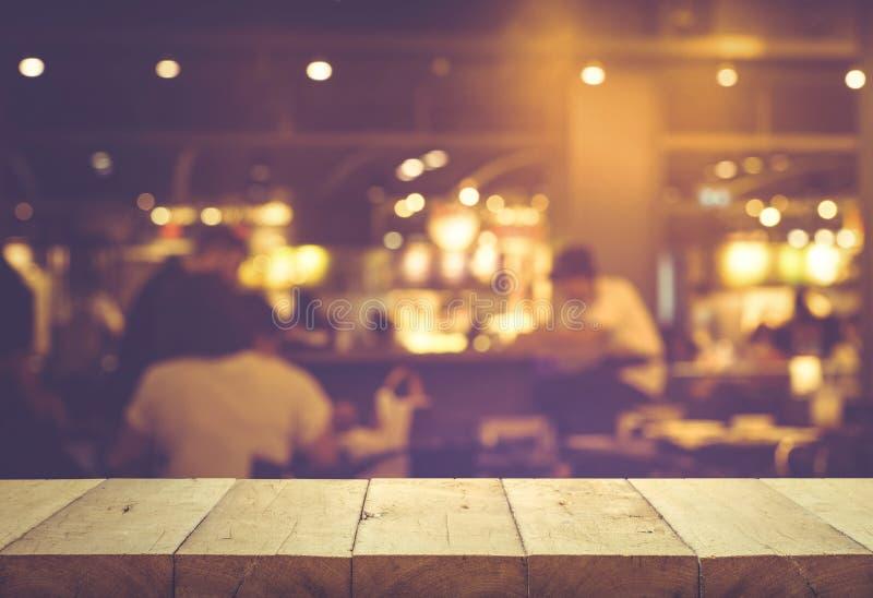 Drewniany stołowego wierzchołka bar z plam ludźmi jest usytuowanym nocy kawiarni, restauracja fotografia royalty free