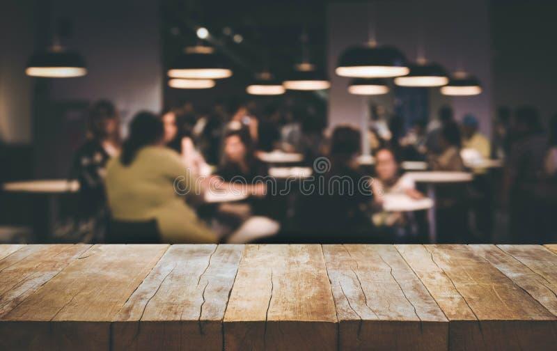 Drewniany stołowego wierzchołka bar z plam ludźmi jest usytuowanym w cukiernianym tle zdjęcia royalty free