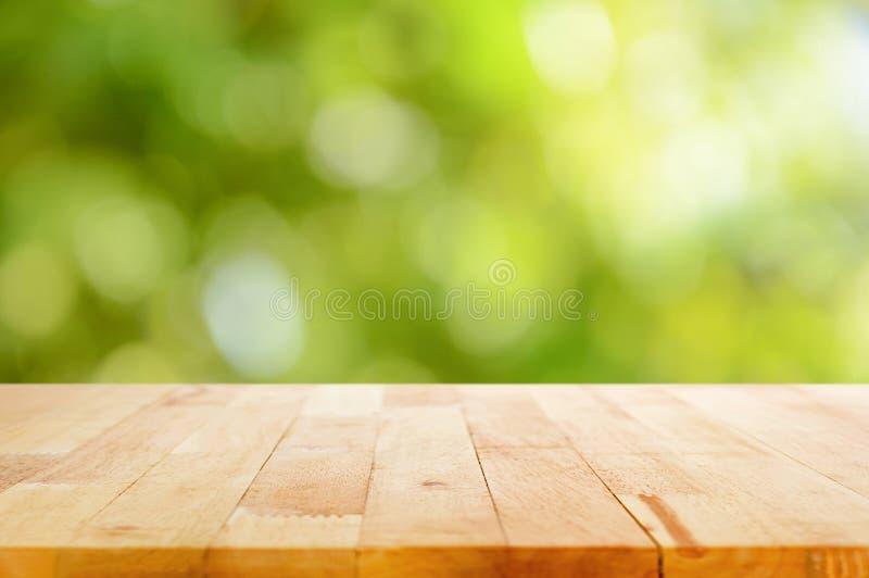 Drewniany stołowy wierzchołek na bokeh abstrakta zieleni tle obrazy royalty free