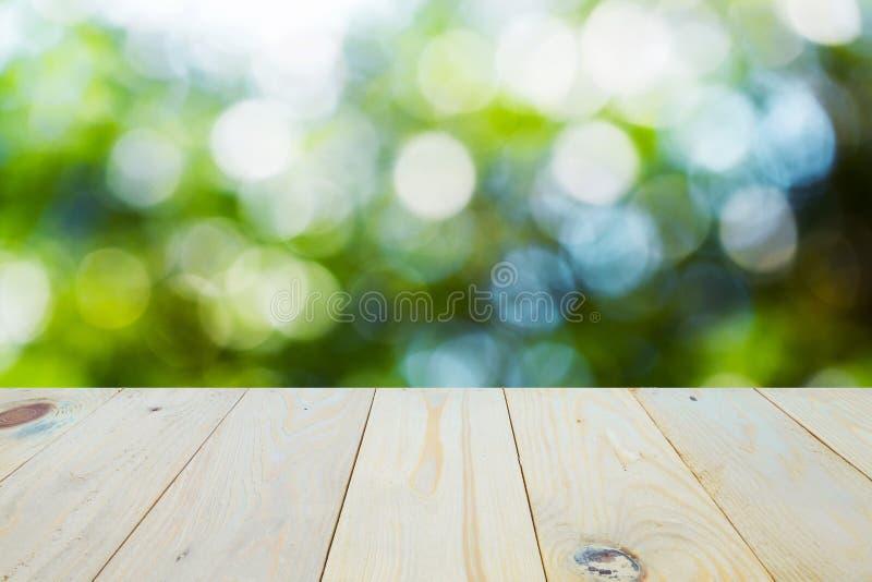 Drewniany stołowy wierzchołek na bokeh zieleni tle zdjęcia royalty free