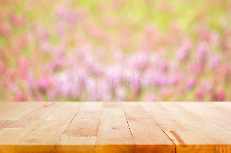 Drewniany stołowy wierzchołek na plama kwiatu ogródu tle