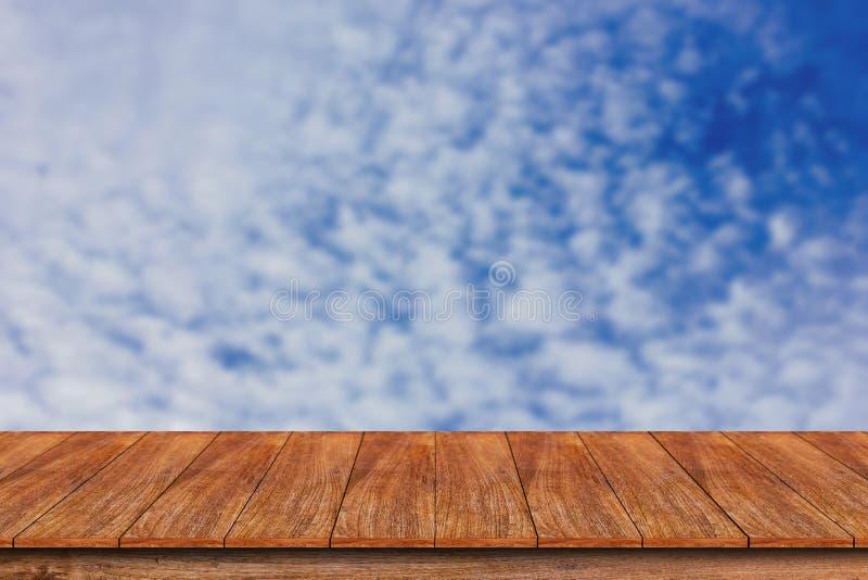 Drewniany stołowy wierzchołek na zamazanym niebieskiego nieba tle fotografia stock