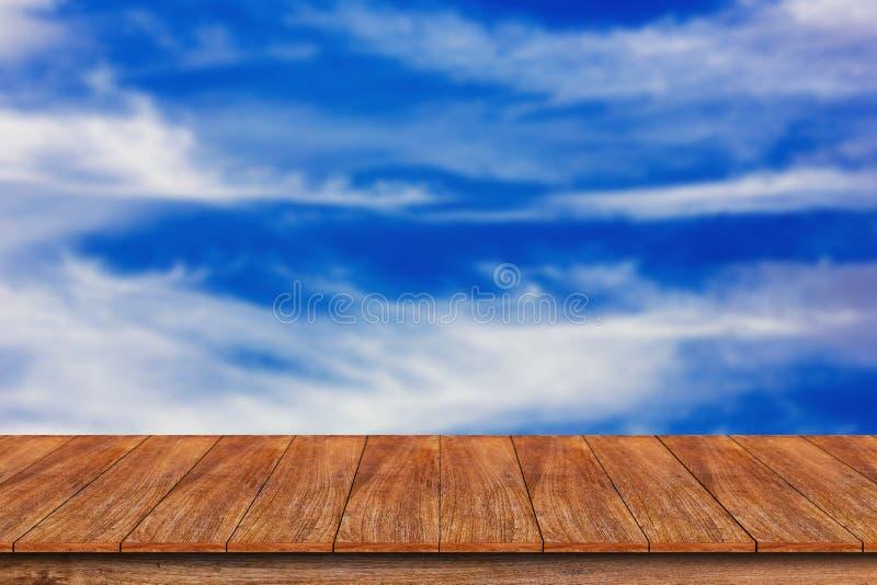 Drewniany stołowy wierzchołek na zamazanym niebieskiego nieba tle obraz stock