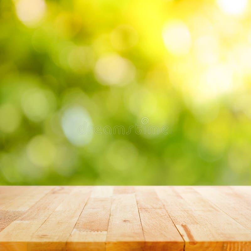 Drewniany stołowy wierzchołek na zielonym bokeh abstrakta tle zdjęcia royalty free