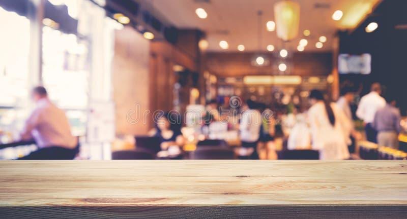 Drewniany stołowy wierzchołek z plamą ludzie w sklep z kawą lub kawiarni, restauracja obraz stock