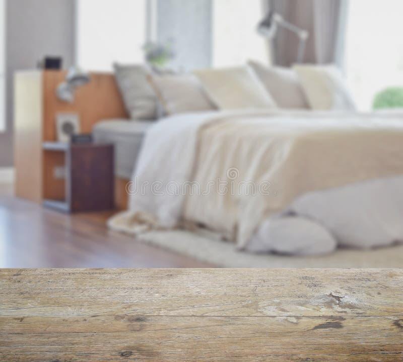 Drewniany stołowy wierzchołek z plamą nowożytny sypialni wnętrze z białymi poduszkami na łóżku zdjęcia royalty free