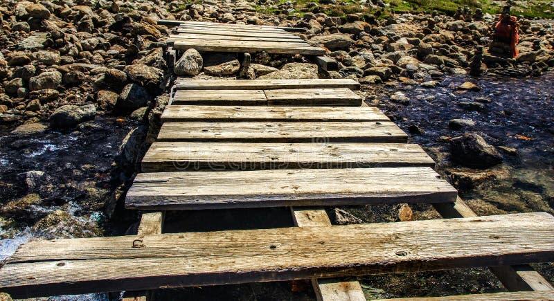 Drewniany stopa most na strumieniu górkowata rzeka z otoczak błękitne wody i skałami zdjęcie stock