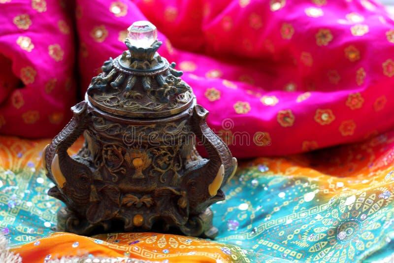 Drewniany szkatuły pudełko z orientalnymi wzorów słoniami pełno złocista biżuteria na Malinowym tkaniny tle fotografia royalty free