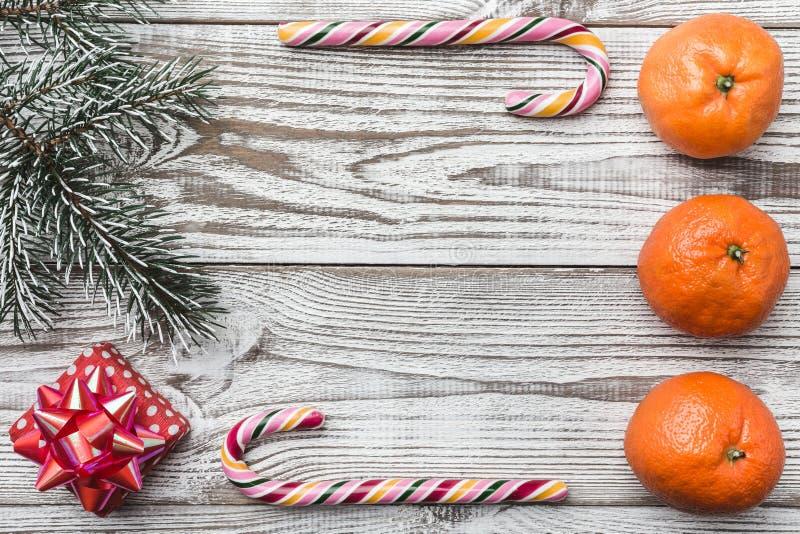Drewniany tło biały Jodły gałąź zieleń Pomarańcze kolorowe cukierki Zimy karta, wakacyjny prezent fotografia royalty free