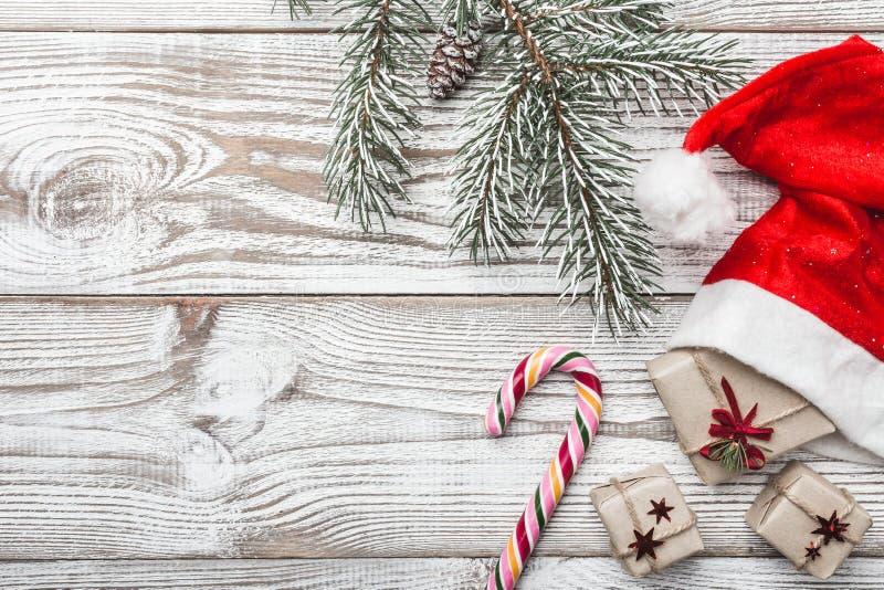 Drewniany tło biały Zimy karta Jego Santa ` s kapelusz dryndula niebieskie oczy, piaskowe słodycze, Jedlinowy drzewo elegancki Pr obrazy stock