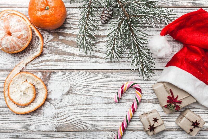 Drewniany tło biały Zimy karta Jego Santa ` s kapelusz dryndula niebieskie oczy, piaskowe słodycze, Jedlinowy drzewo mandarynki P zdjęcie stock
