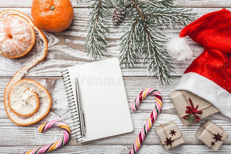 Drewniany tło biały Zimy karta Jego Santa ` s kapelusz dryndula sweets kolor Jedlinowy drzewo mandarynki Gratulacje karta dla fotografia royalty free