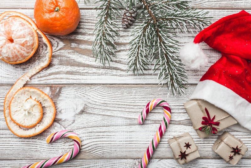 Drewniany tło biały Zimy karta Jego Santa ` s kapelusz dryndula sweets kolor Jedlinowy drzewo mandarynki Przestrzeń dla kartka z  zdjęcie royalty free