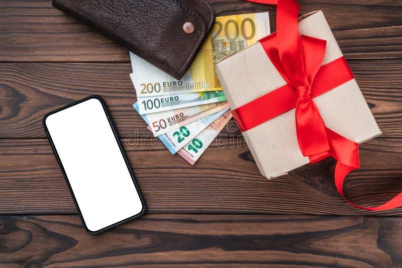 Drewniany tło, pieniądze różna wartość, portfla telefon i cena prezent, Odgórny widok obraz royalty free