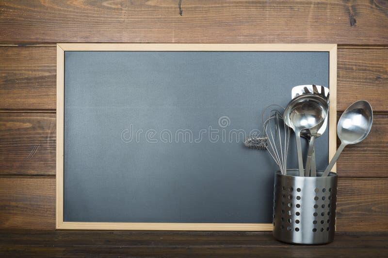 Drewniany tło z kulinarnymi naczyniami i chalkboard obraz stock