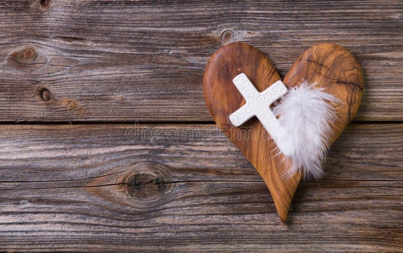 Drewniany tło z oliwnym sercem i biel krzyżujemy dla obitua fotografia royalty free
