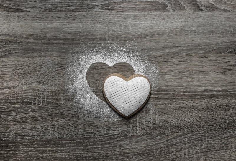 Drewniany tło z sproszkowanym prochowym śniegiem sylwetka serce nalewa pod sylwetek kłamstwami ciastko forma serce obrazy royalty free