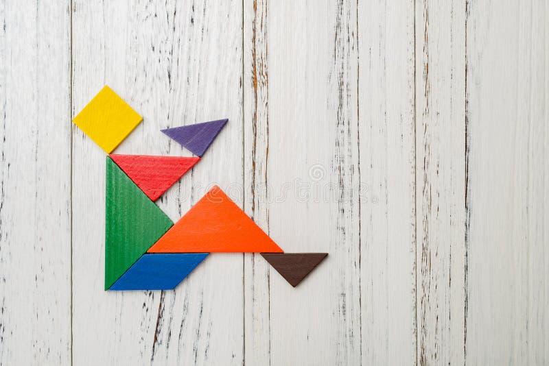 Drewniany tangram kształtował jak ludzi siedzącego puszka i pić zdjęcia stock