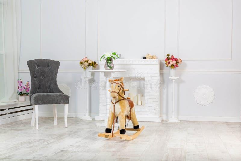Drewniany TARGET1214_0_ Ko? Zabawka stojaki na tle dekoracyjna graby i światła ściana, szarość przewodniczą blisko go zdjęcie stock