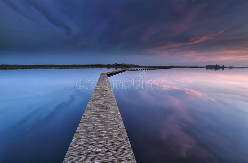 Drewniany walkpath na wodzie przy świtem fotografia stock