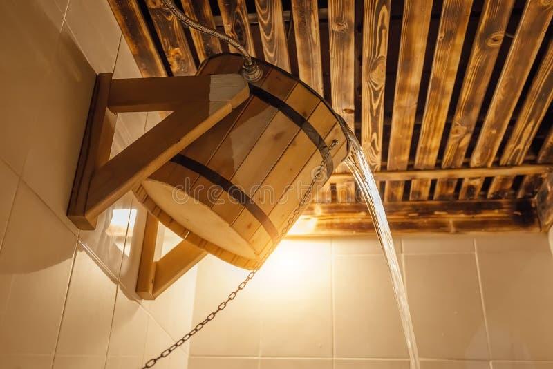 Drewniany wiadro dla rosjanina sauna lub skąpania Zimna woda nalewa od wiadra w parowym pokoju zdjęcie stock