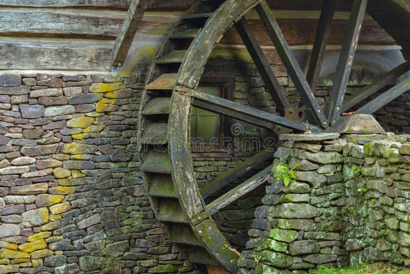 Drewniany wodny paddle koło i mechaci kamienie na stronie stary obrazy royalty free