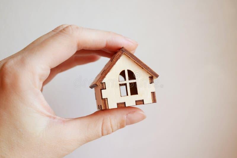Drewniany zabawka domu model w kobiety ręce na białego tła frontowym widoku obrazy royalty free