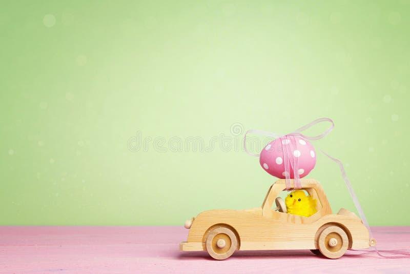 Drewniany zabawkarski samochód z Wielkanocnym jajkiem na dachowym i pisklęcym kierowcy na g zdjęcie royalty free