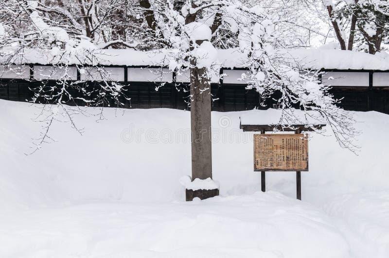 Drewniany znak przy Hirosaki kasztelem w zima sezonie, zakrywającym z wh zdjęcia royalty free