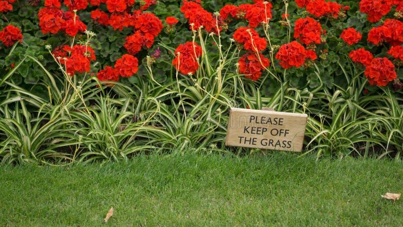 Drewniany znak radzi Zadawalać utrzymanie z trawy, z zieloną trawą w przedpolu i kwiatu łóżkiem z czerwienią kwitnie w b zdjęcie royalty free