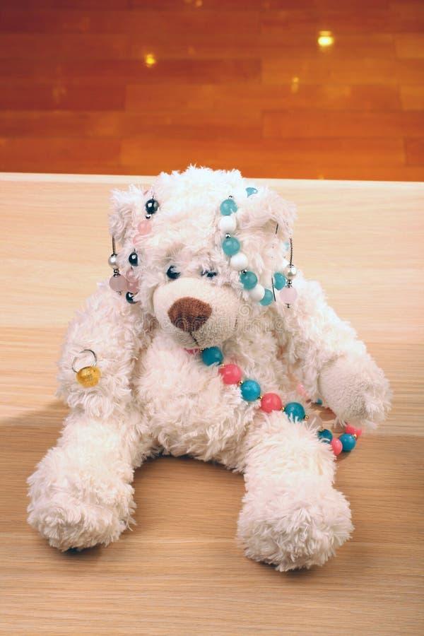 Drewnianych stół zabawki niedźwiedzia menchii agata kamienia koralików bransoletki Murano szkła biały ceramiczny pierścionek zdjęcia royalty free