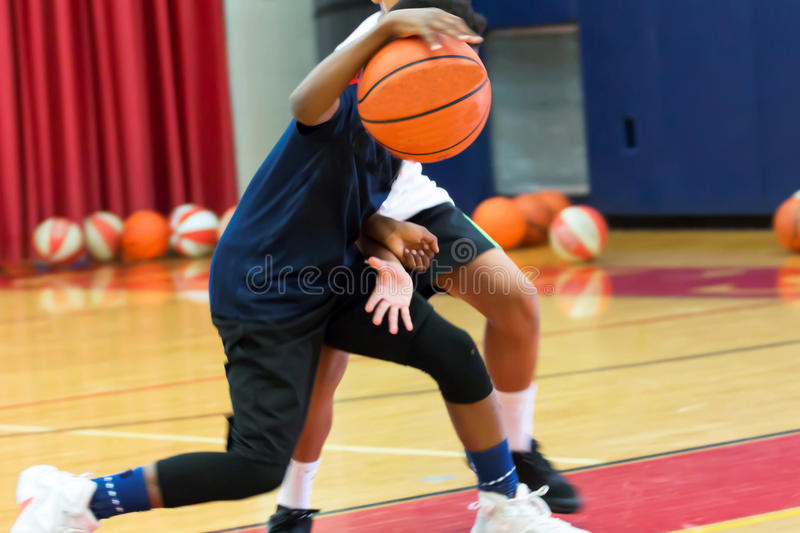 Dribbling a basketball at summer camp. Two teenage male basketball players doing a one on one drill indoors at a local basketball camp over the summer stock photos