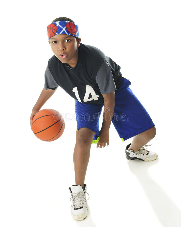 Dribbling Tween. An African American tween basketball player actively dribbling his ball. On a white background stock photo