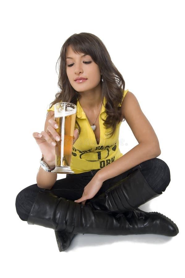 Dricka öl för nätt flicka från exponeringsglaset royaltyfri fotografi