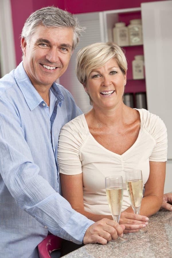 Dricka champagne för man- & kvinnapar i kök arkivfoto