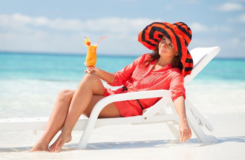 Dricka coctail för kvinna på stranden royaltyfri bild