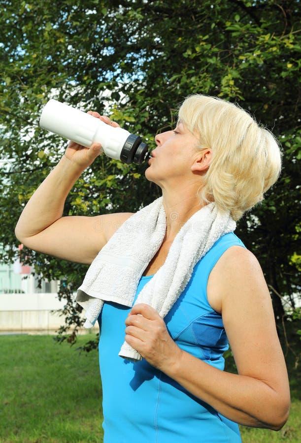 Dricka den höga frun med vattenflaskan och handduken som gör sporten royaltyfri fotografi