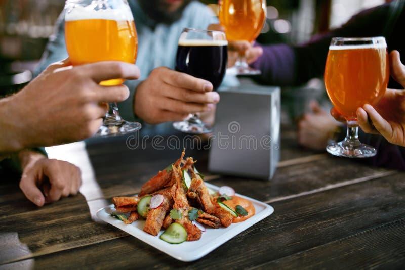 dricka för öl Vänner som lyfter exponeringsglas av öl royaltyfria bilder