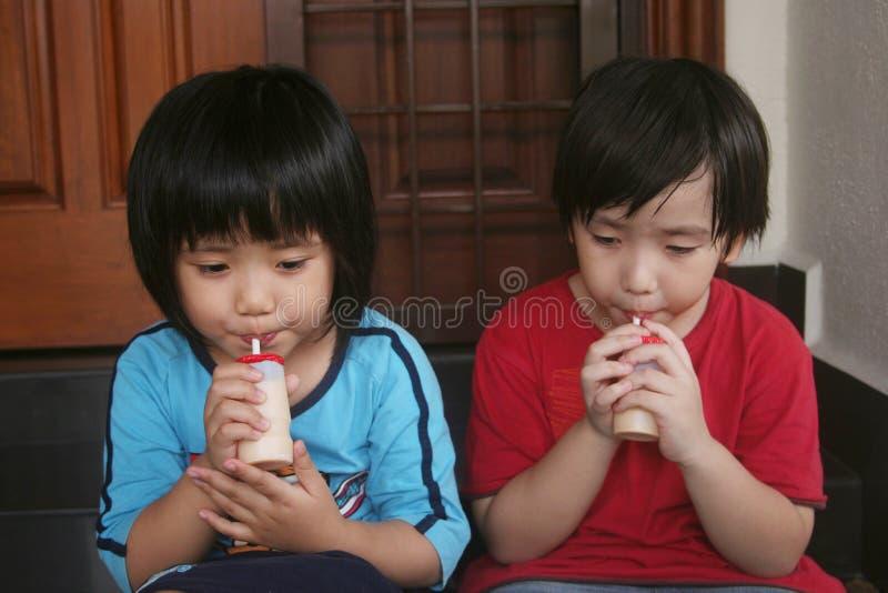 dricka flickayoghurt för pojke royaltyfri foto