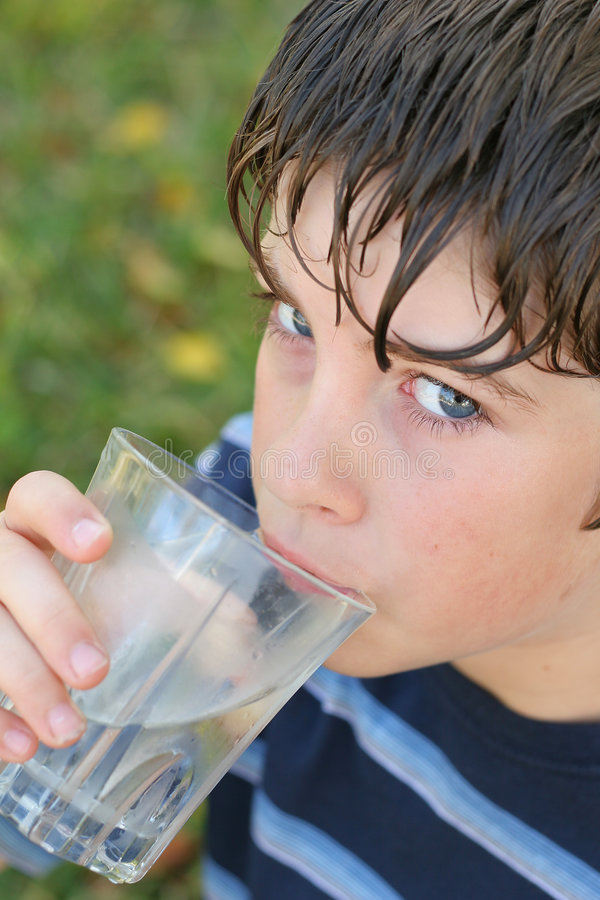 dricka glass vatten för pojke royaltyfri foto