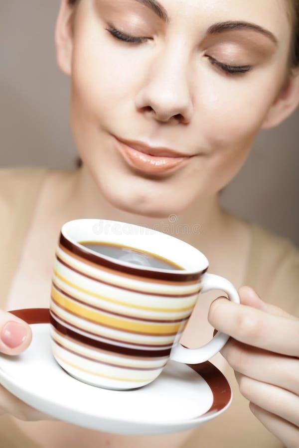 Dricka kaffe för ung nätt kvinna royaltyfria bilder