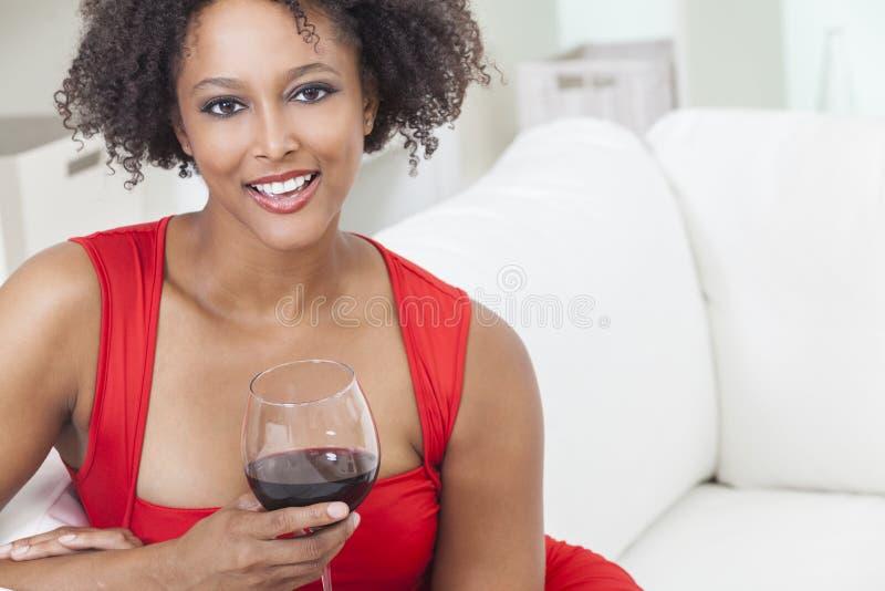 Dricka rött vin för afrikansk amerikanflickakvinna arkivfoto