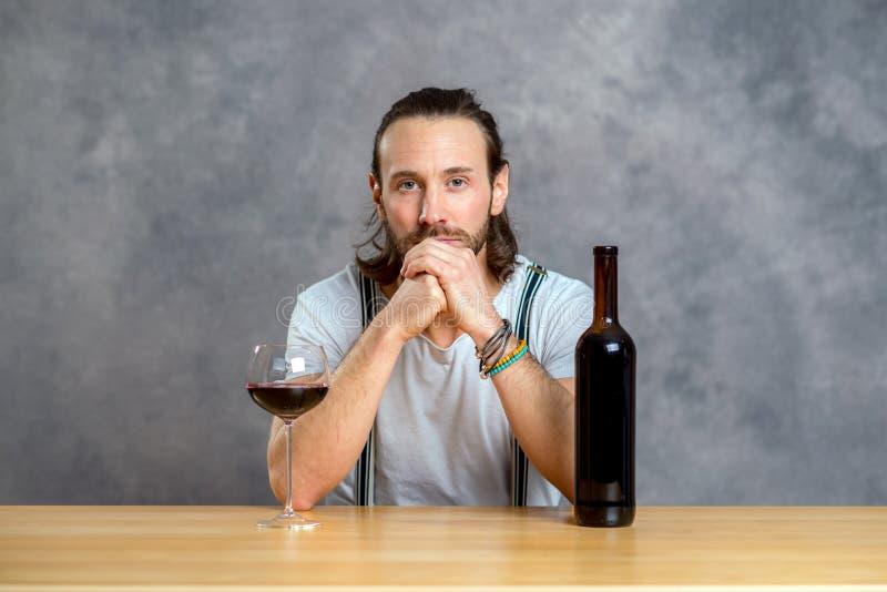 Dricka rött vin för ung man arkivbild