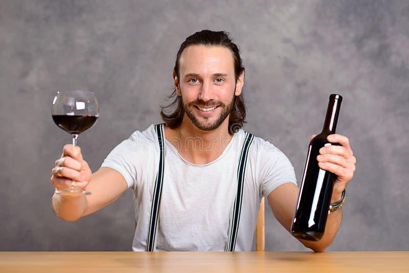 Dricka rött vin för ung man royaltyfri bild